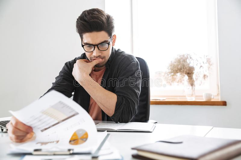 Concentrated handsome man in eyeglasses working with documents. While sitting by the table at office stock photo