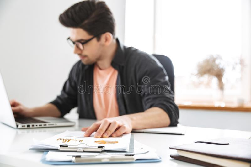 Concentrated handsome man in eyeglasses working with laptop computer royalty free stock images