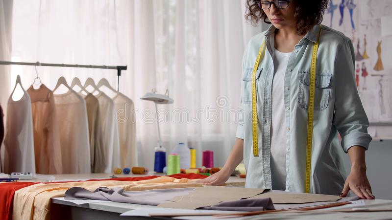 Concentrated on her work designer unfolding fabric on desk, personal atelier. Stock photo stock photography