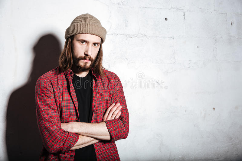 Concentrated hipster man wearing hat looking at camera. royalty free stock image