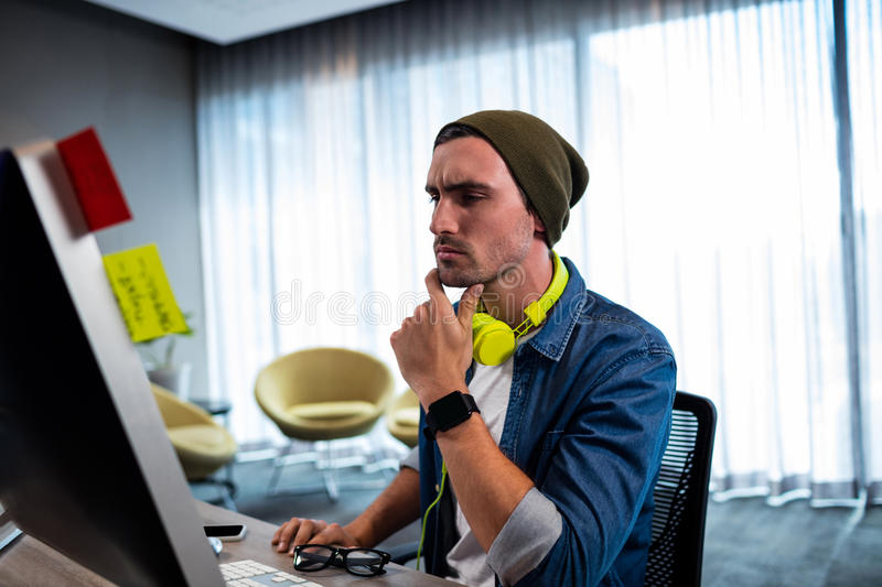 Concentrated hipster man working with audio headset royalty free stock image