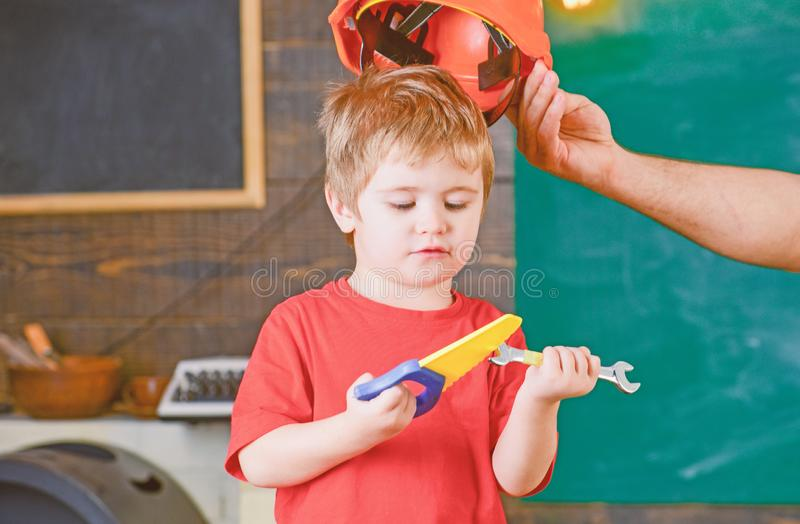 Concentrated kid looking down at tools in his hands. Boy learning new skills. Daddy taking off helmet from son.  stock images