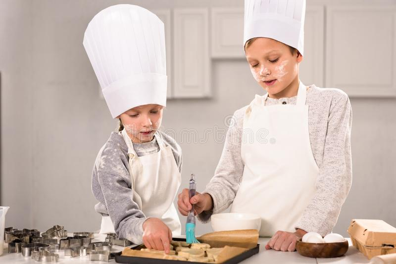 Concentrated kids in aprons brushing cookies on baking tray. In kitchen stock image