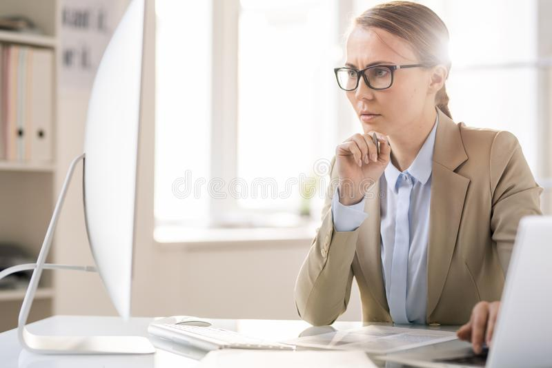Concentrated lady analyzing documents. Serious concentrated beautiful young lady in jacket sitting at table and frowning eyebrows while analyzing online stock photo