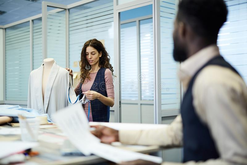 Concentrated lady saying measurements of jacket to tailor stock images