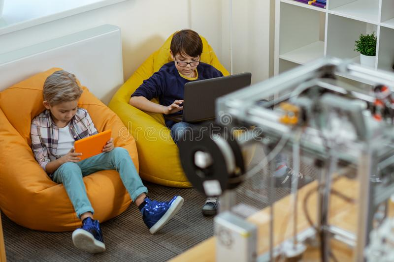 Concentrated little boys comfortably sitting in bright chairs bags. Young scientists. Concentrated little boys comfortably sitting in bright chairs bags and stock images