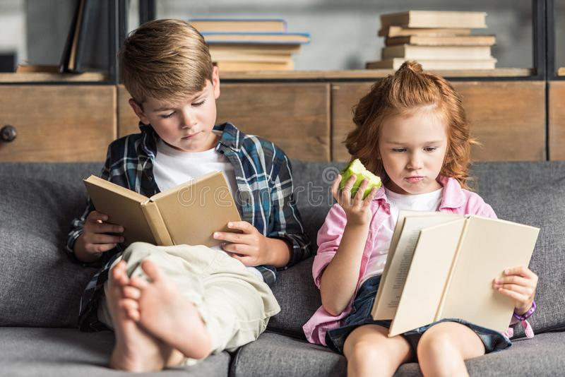 concentrated little brother and sister reading books on couch stock photos