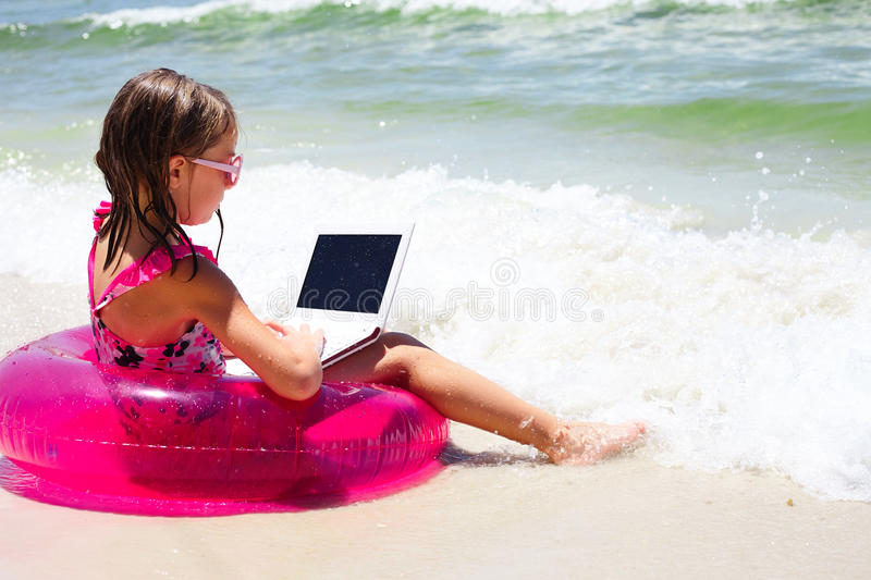 Concentrated little girl using laptop on beach stock photos