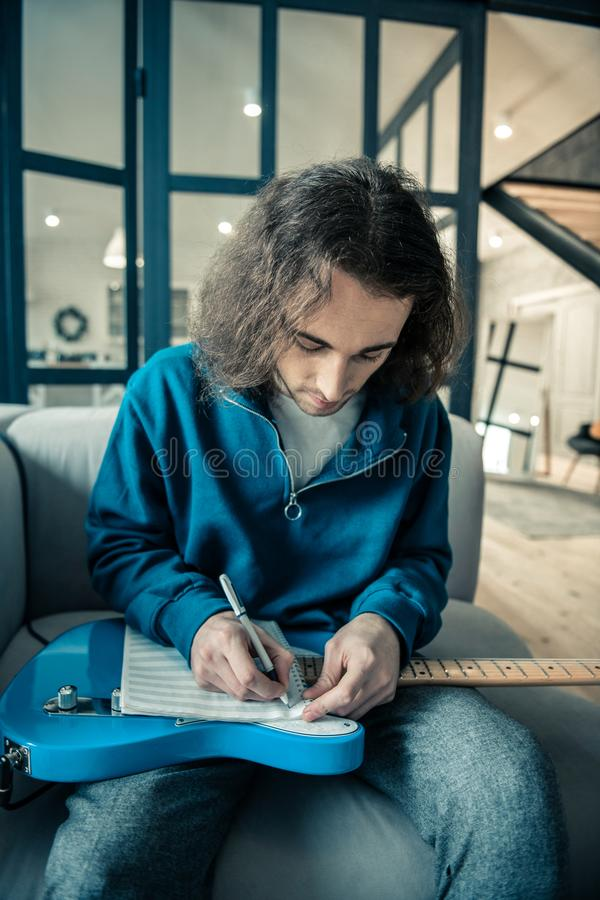 Concentrated Long-haired man putting notebook on his bright guitar. Daily repetition. Concentrated Long-haired man putting notebook on his bright guitar and royalty free stock image