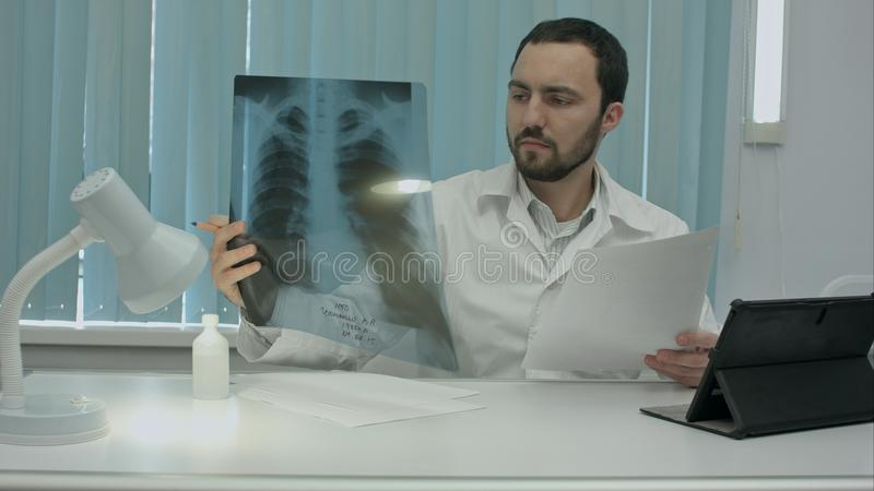 Concentrated male doctor looking at x-ray picture in the medical office. Concentrated male doctor looking at x-ray picture in the white medical office, seating royalty free stock image