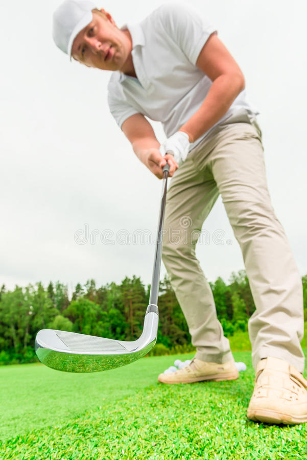 Concentrated male golfer with a golf club stock images
