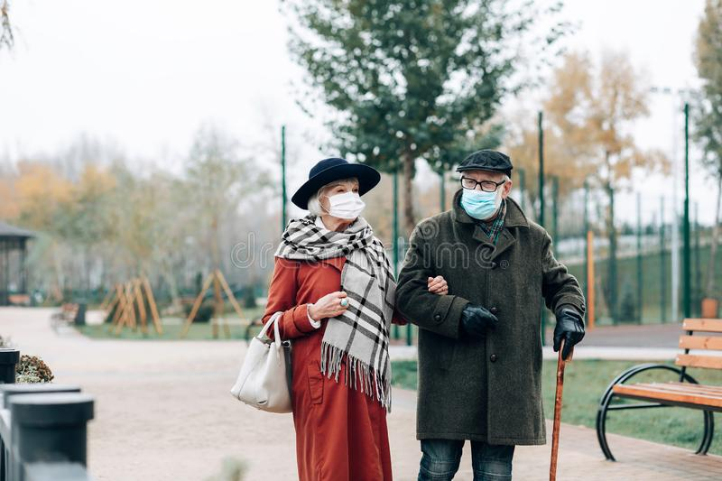 Concentrated male person listening to his wife. On walk. Attractive mature women wearing sterile mask while spending time outdoors royalty free stock photos