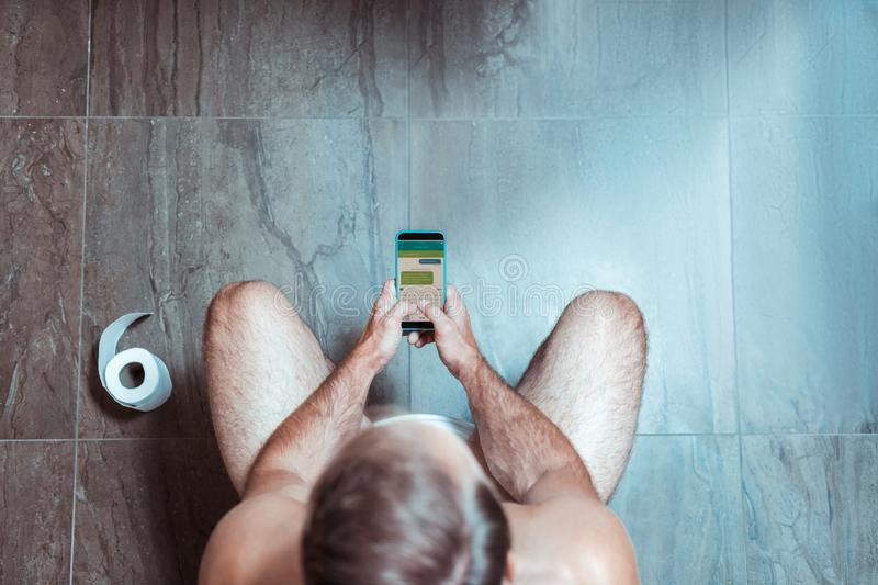 Concentrated man being on his phone while sitting on the toilet royalty free stock images