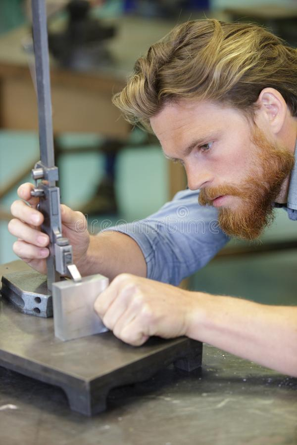 Concentrated man measuring panel with metal liner stock photography