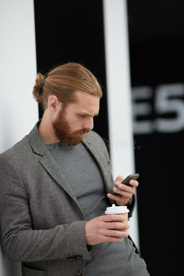 Concentrated man reading sms. Concentrated red-bearded man in jacket leaning on wall and reading sms on smartphone while drinking coffee in lobby royalty free stock photos