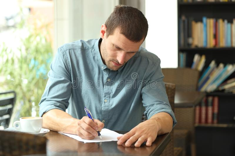 Concentrated man writing notes in a paper in a coffee shop royalty free stock photos