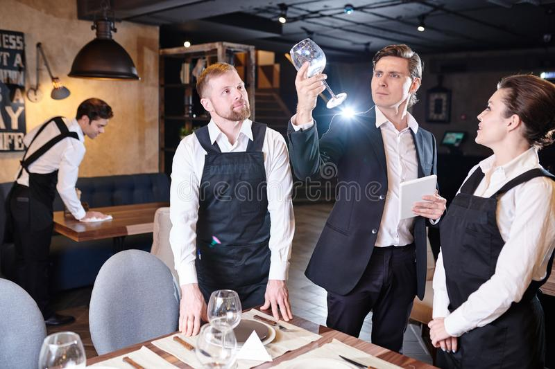 Concentrated manager checking wineglass while waiters serving ta stock photography