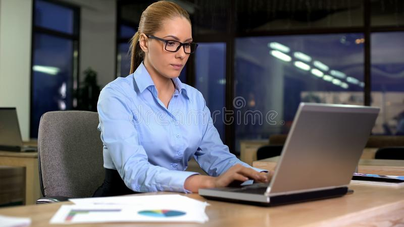 Concentrated manager working on laptop at night shift in office, extra hours. Stock photo stock image