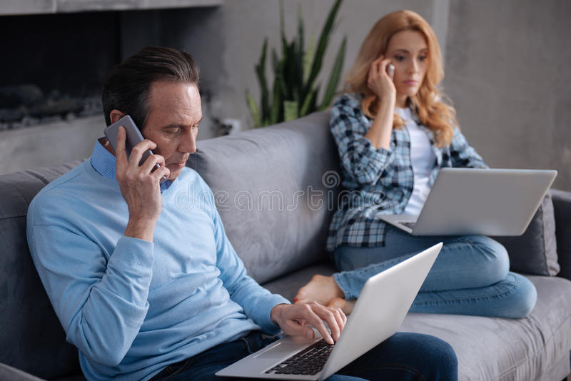 Concentrated mature couple using gadgets at home. Highest priority giving to the career . Mature busy skillful couple sitting on the couch at home and using royalty free stock photo