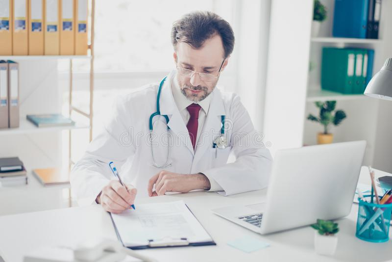 Concentrated mature doctor is writing down the details of disease. He is in a white coat, glasses, sitting in modern work station royalty free stock photos
