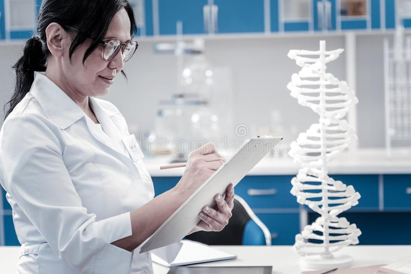 Concentrated mature lady writing something down in laboratory royalty free stock image