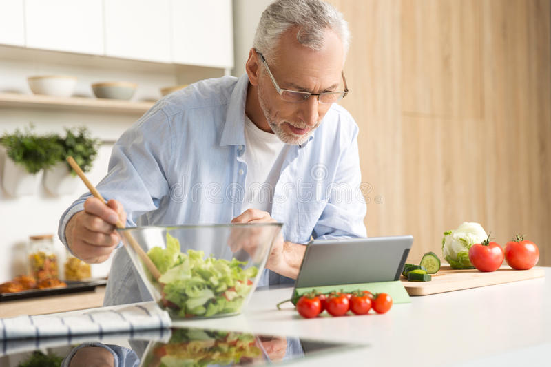 Concentrated mature man cooking salad using tablet stock photo