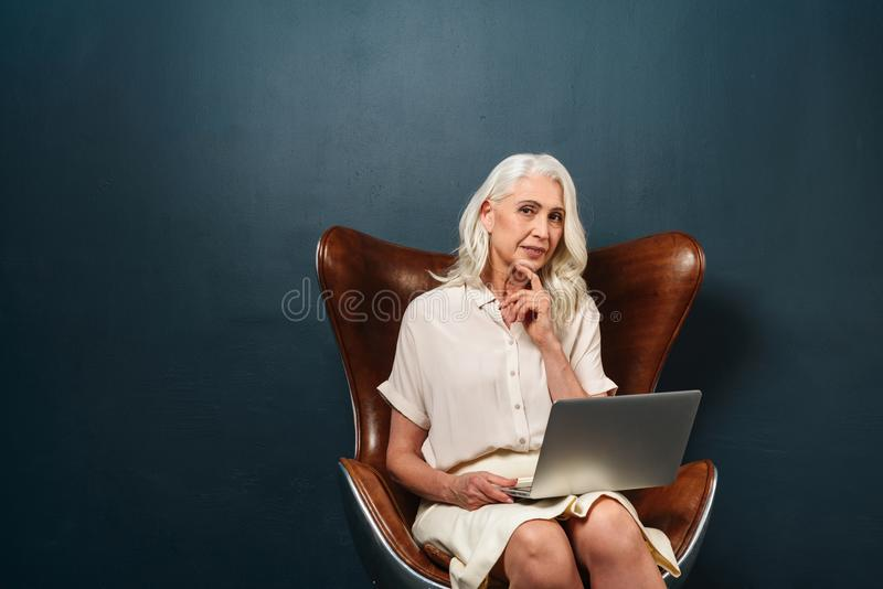 Concentrated mature old woman using laptop computer. stock photo