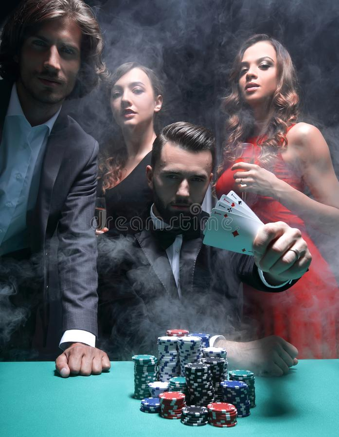 Concentrated men and women playing poker in casino. Young handsome men sitting behind poker table with card stock photo