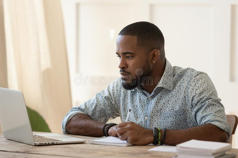 Concentrated millennial african american guy focused on online university courses. royalty free stock photography