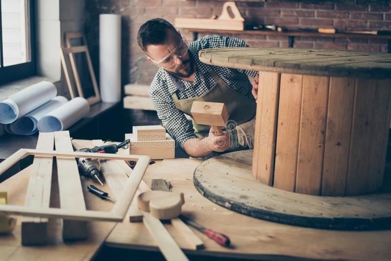 Concentrated minded thoughtful pensive handsome bearded hardworking joiner is checking a wooden coil with a chisel in his royalty free stock images