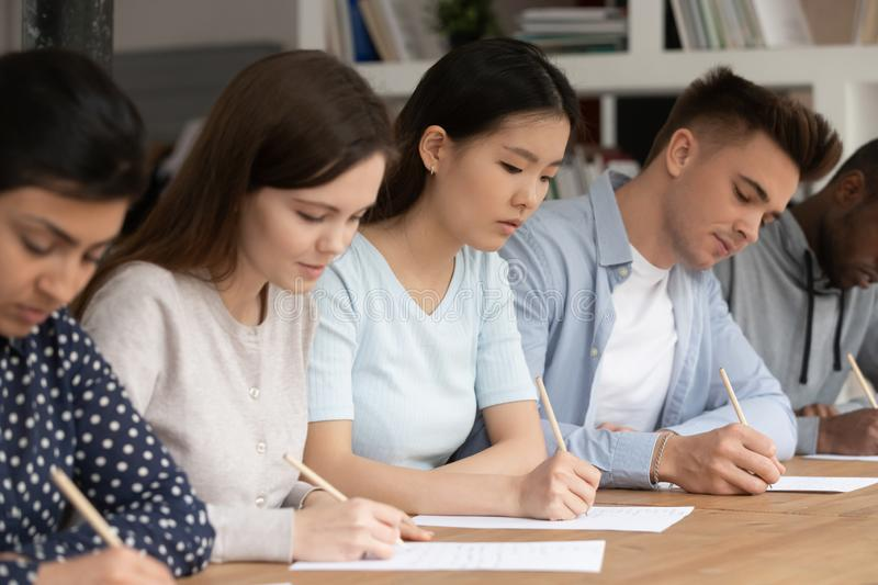 Concentrated mixed race students passing evaluation examination during session. royalty free stock photography