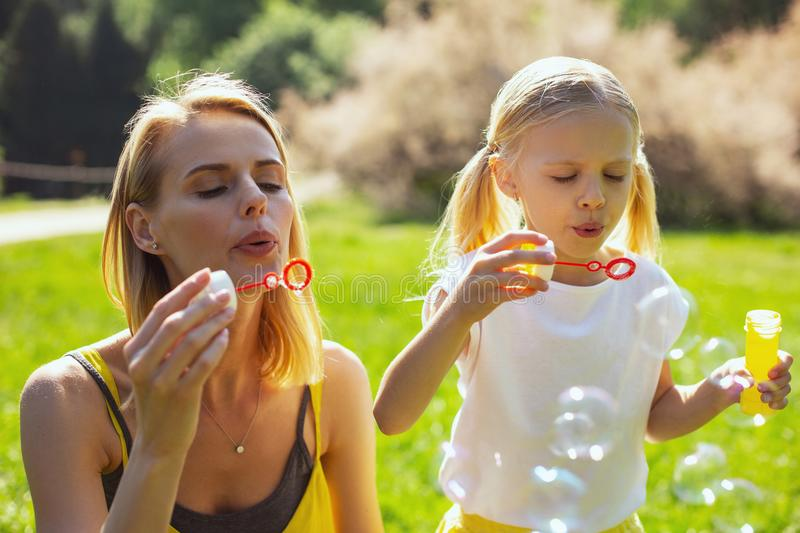 Concentrated mommy blowing bubbles wither daughter stock photo