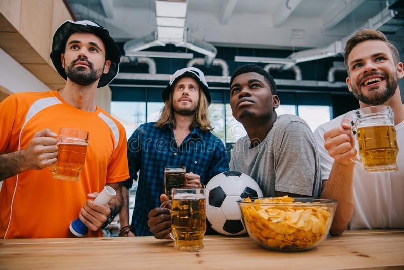concentrated multicultural group of male football fans with beer watching soccer match stock images