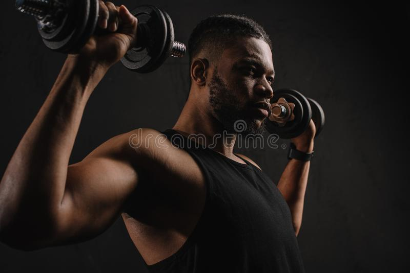 concentrated muscular african american man exercising with dumbbells stock photography