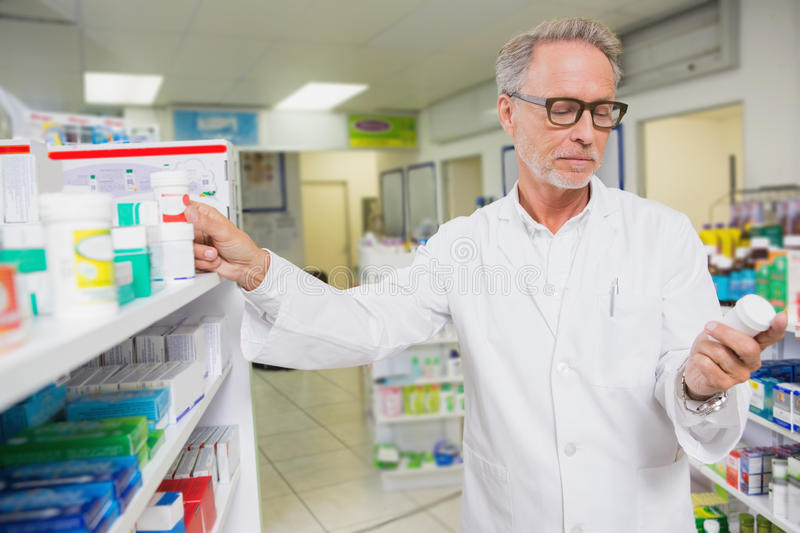 Concentrated pharmacist looking at medicine royalty free stock image
