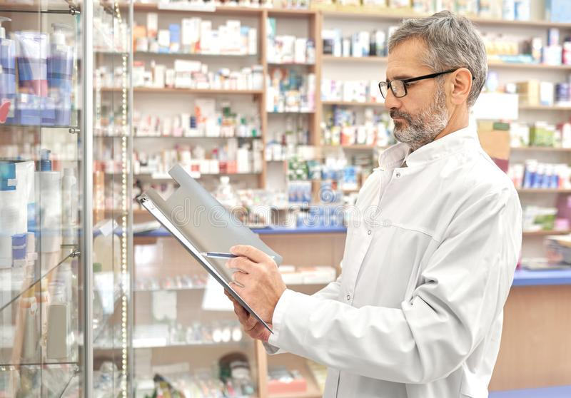 Pharmacist standing in drugstore with folder in hands. Concentrated pharmacist standing in drugstore near shelves with different medicaments. Chemist holding royalty free stock image