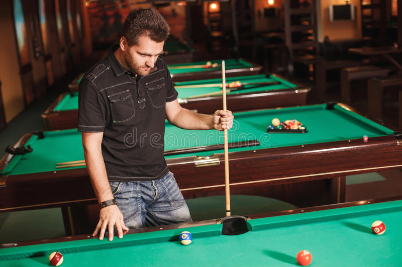 Concentrated player with a cue in billiard room. Playing billiards stock photos