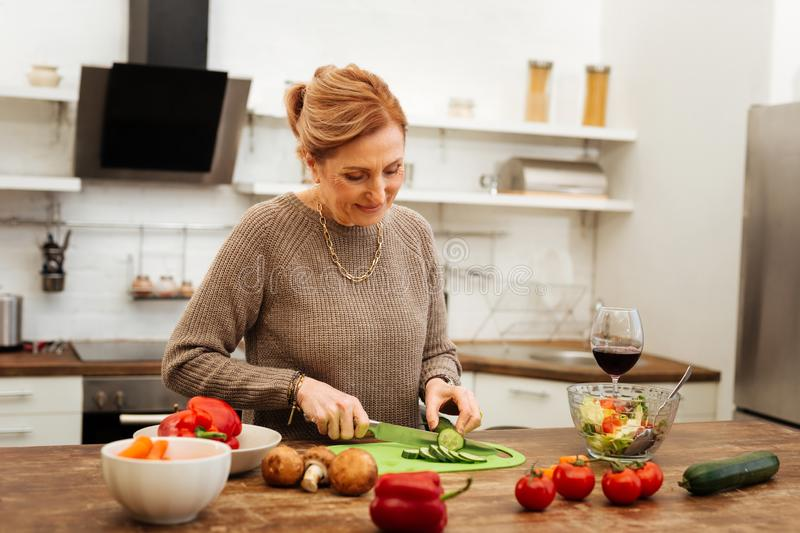 Concentrated pleasant lady in gold jewelry staying in kitchen. Ingredients for salad. Concentrated pleasant lady in gold jewelry staying in kitchen and cutting stock images