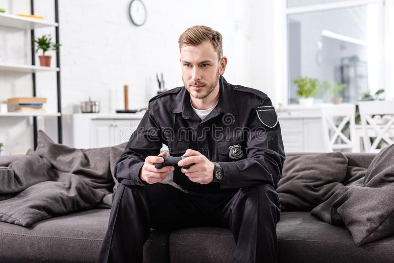 Concentrated policeman with gamepad sitting on couch and. Playing video game stock photos
