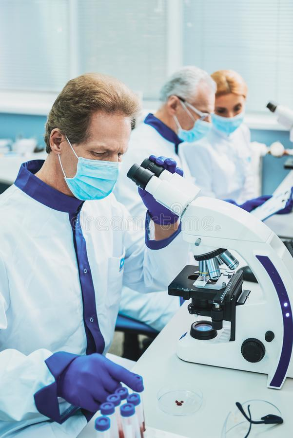 Concentrated practitioner sitting at his workplace. Medical study. Professional scientist being well equipped while looking at samples royalty free stock image