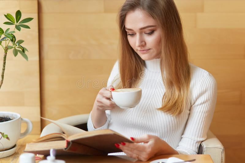 Concentrated pretty young woman reads book with cup of cappuccino, focused on reading, enjoys interesting exciting novel, poses in. Cafeteria, dressed in white stock photo