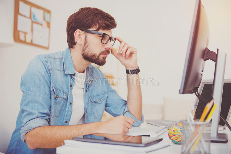 Concentrated programmer looking at the computer. Where is the mistake. Concentrated young handsome programmer wearing glasses and looking at the monitor looking stock images