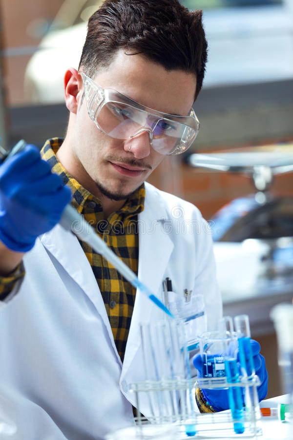 Concentrated scientist making experiment in laboratory. Portrait of concentrated scientist making experiment in laboratory royalty free stock image