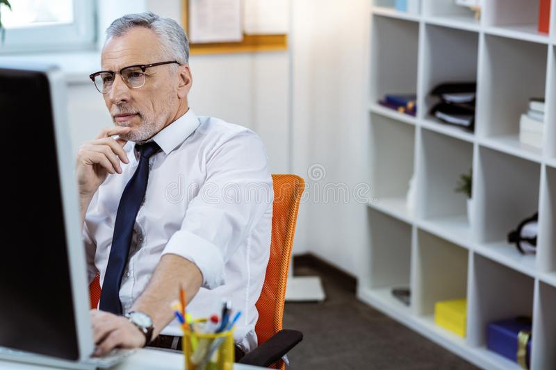 Concentrated senior man with grey beard wearing white shirt. Resolute man. Concentrated senior man with grey beard wearing white shirt and working with computer royalty free stock photo
