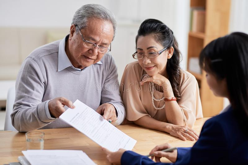 Studying Real Estate Purchase Agreement. Concentrated senior men and his pretty wife studying terms of real estate purchase agreement while having meeting with stock image