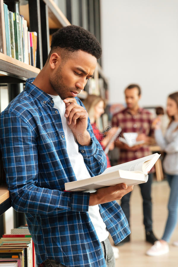 Concentrated serious african man reading book stock image