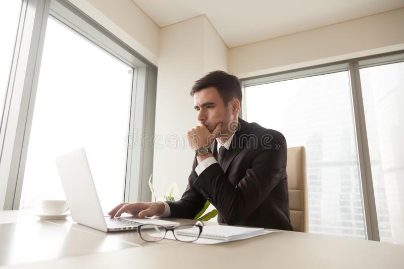 Concentrated serious businessman using laptop computer, working royalty free stock photo