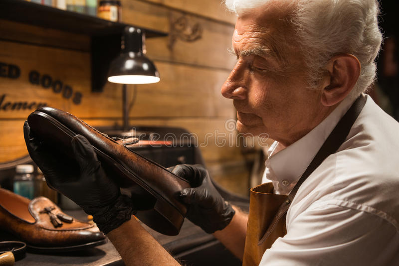 Concentrated shoemaker in workshop making shoes. Image of mature concentrated shoemaker in workshop making shoes. Looking aside royalty free stock photos