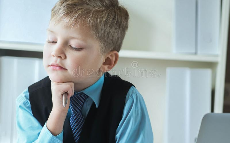 Concentrated small boy in suit thinking about money and budget increasing ways. Little financial director. Concentrated small boy in suit thinking about money stock image