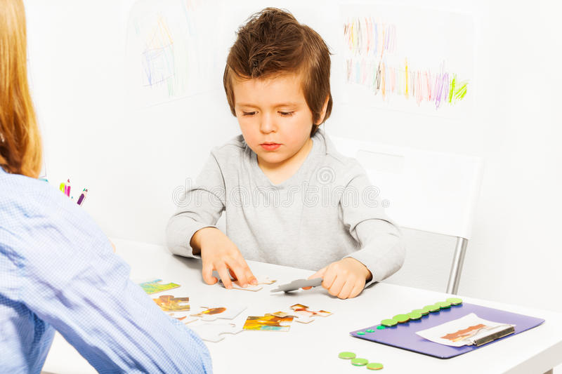 Concentrated solve puzzle during developing game. Concentrated boy solve puzzle cards during developing game at the table with his parent indoors with ABA stock image